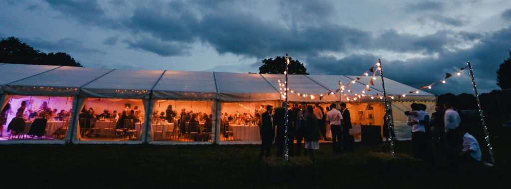 Dry hire marquee at dusk with guests enjoying the wedding celebrations