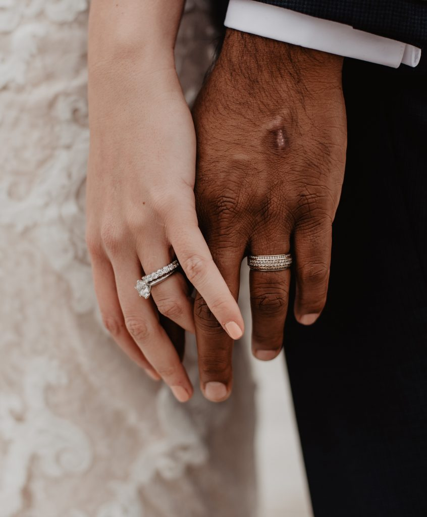 A couples hands gently touching and showing their ethical wedding bands