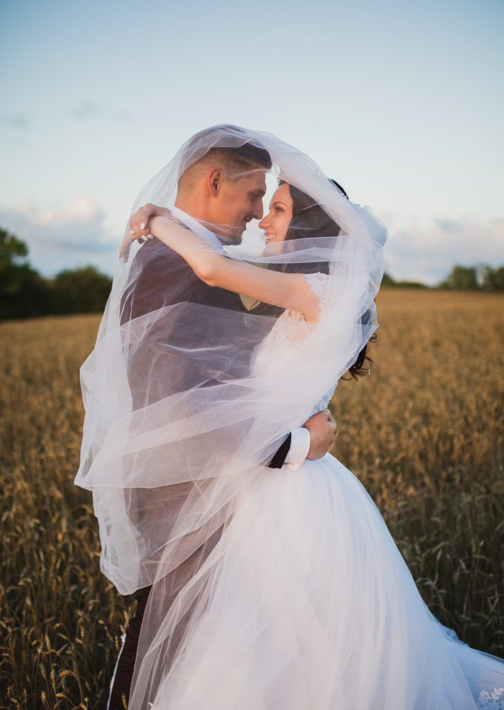 Married couple in a wheat field romantically cuddling with the veil wrapped around them