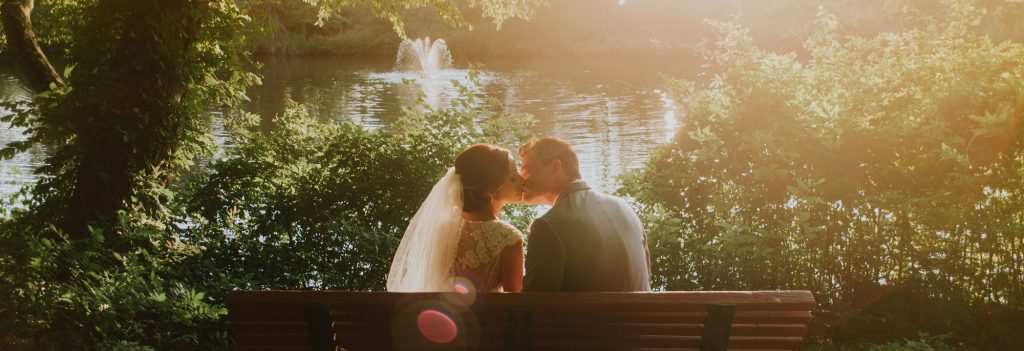 wedding couple sat kissing by a lake in golden hour sunlight