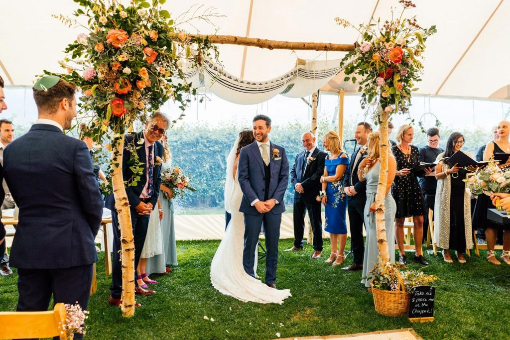 A Jewish Cermony Chuppah decorated with eco-friendly foraged florals and foliage in peach and white tones