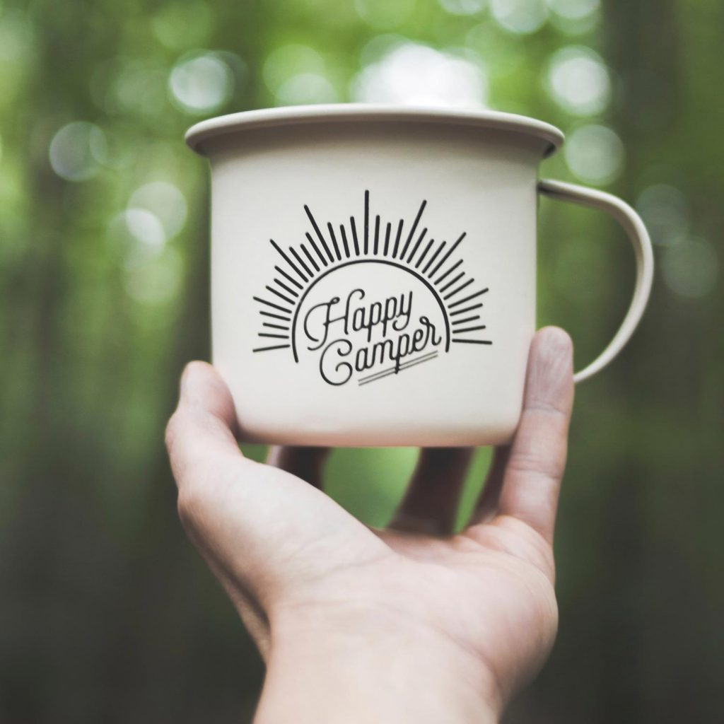 A mug saying Happy Camper being held up whilst in a woodland background