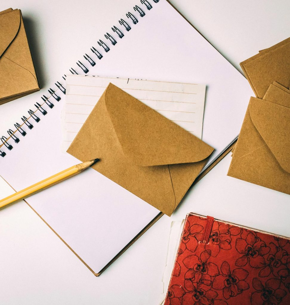 A notebook, pencil and small envelopes ready for writing and collecting date night ideas