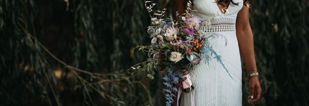 Eco-friendly wedding bouquet featuring foraged florals and foliage in blue's and mauve's and white's
