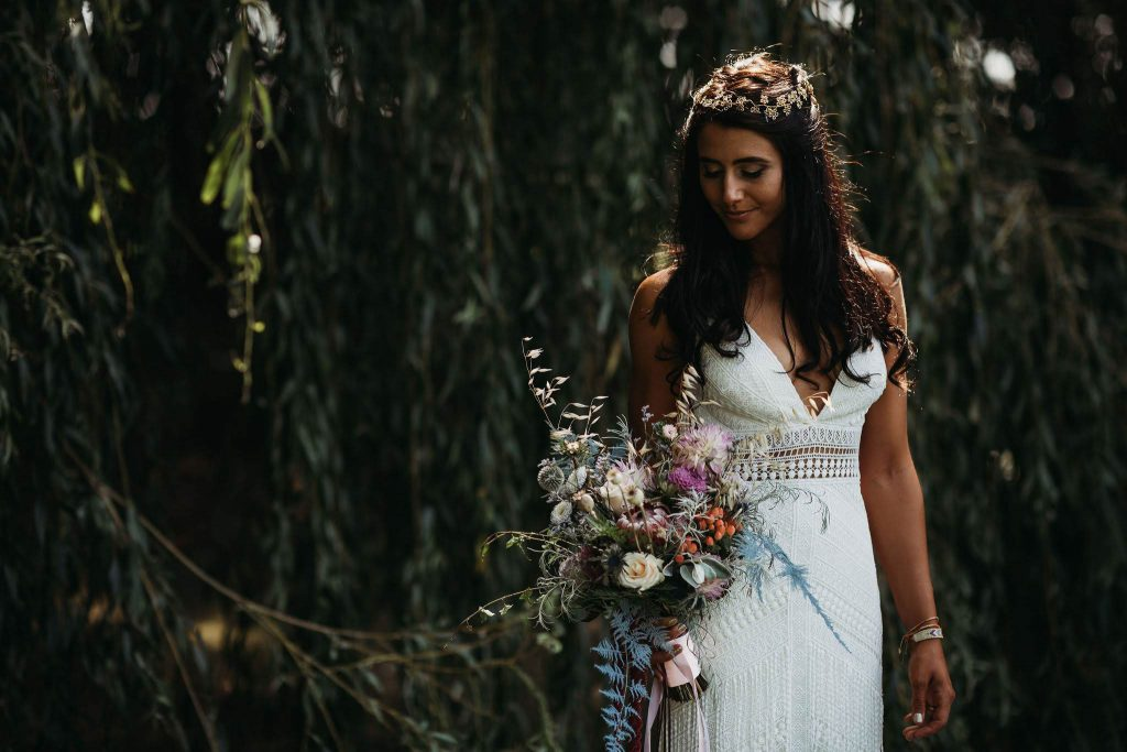 Bohemian bride holding her free flowing bouquet of foraged foliage and flowers