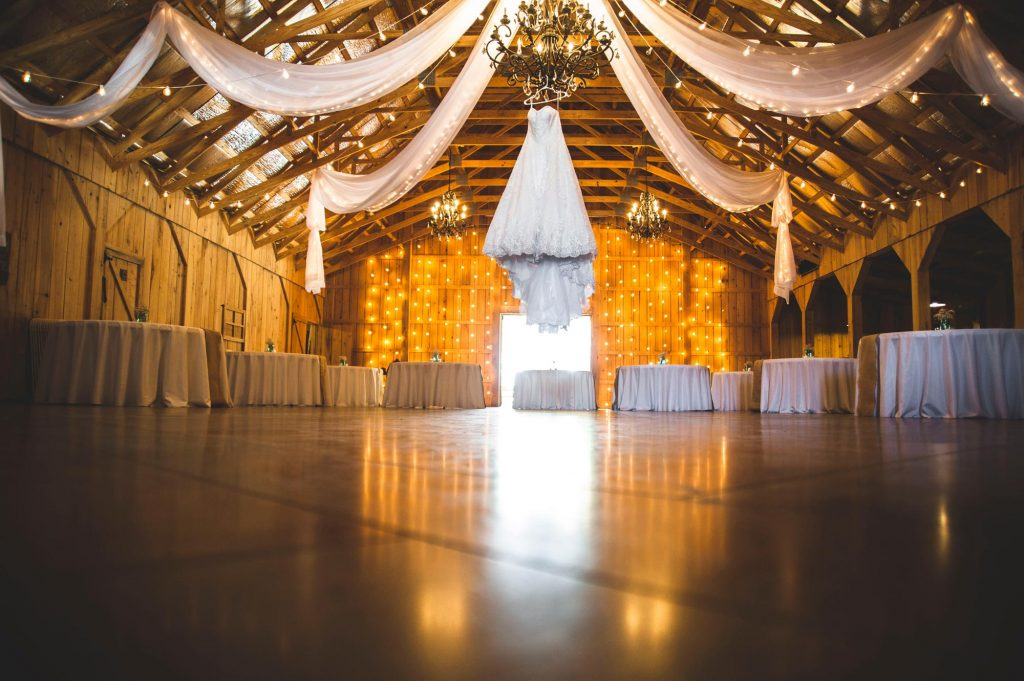 Dry hire barn venue set up for a wedding reception with fairy lights and ceiling drapes
