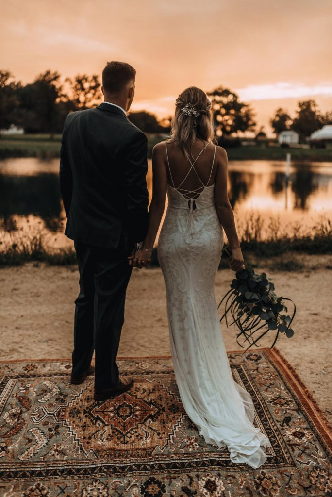 Newlyweds looking across a pond to their outdoor wedding venue site at sunset