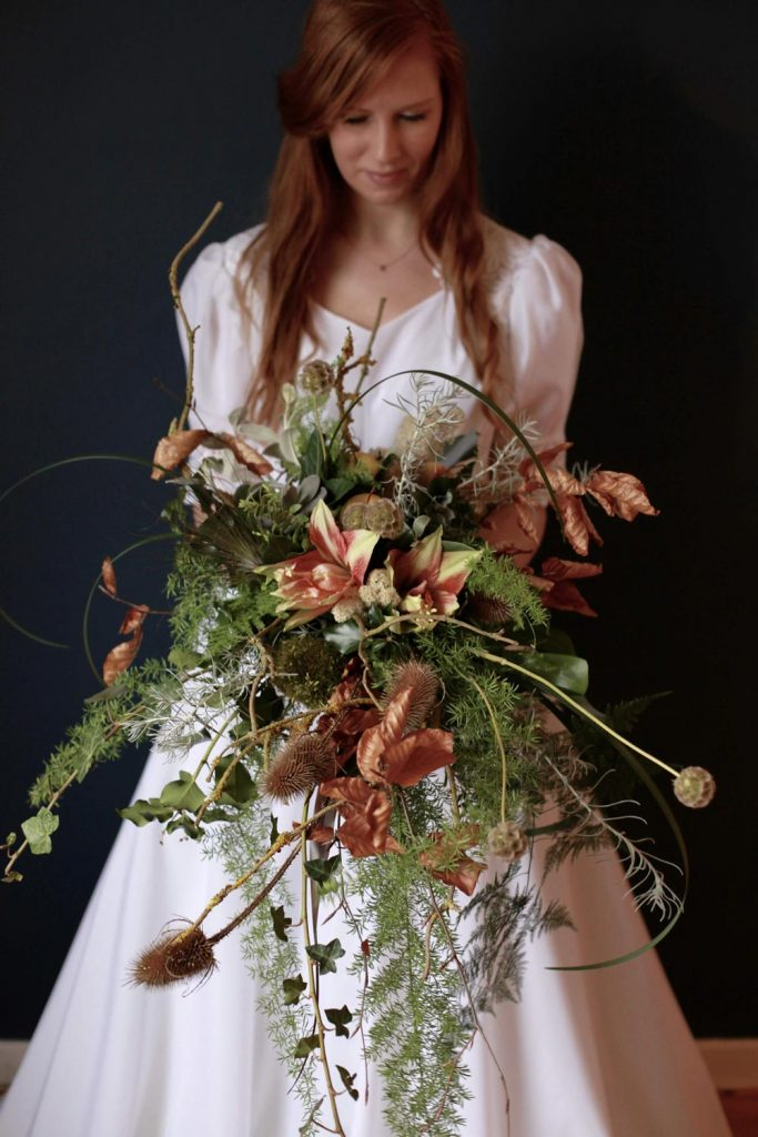 Bride holding her bouquet full of foraged teasels and eco-friendly florals in autumnal and winter shades