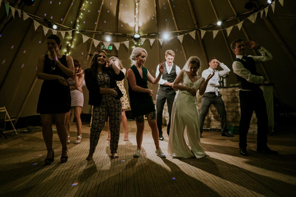 Guests dancing with the bride and groom inside a tipi