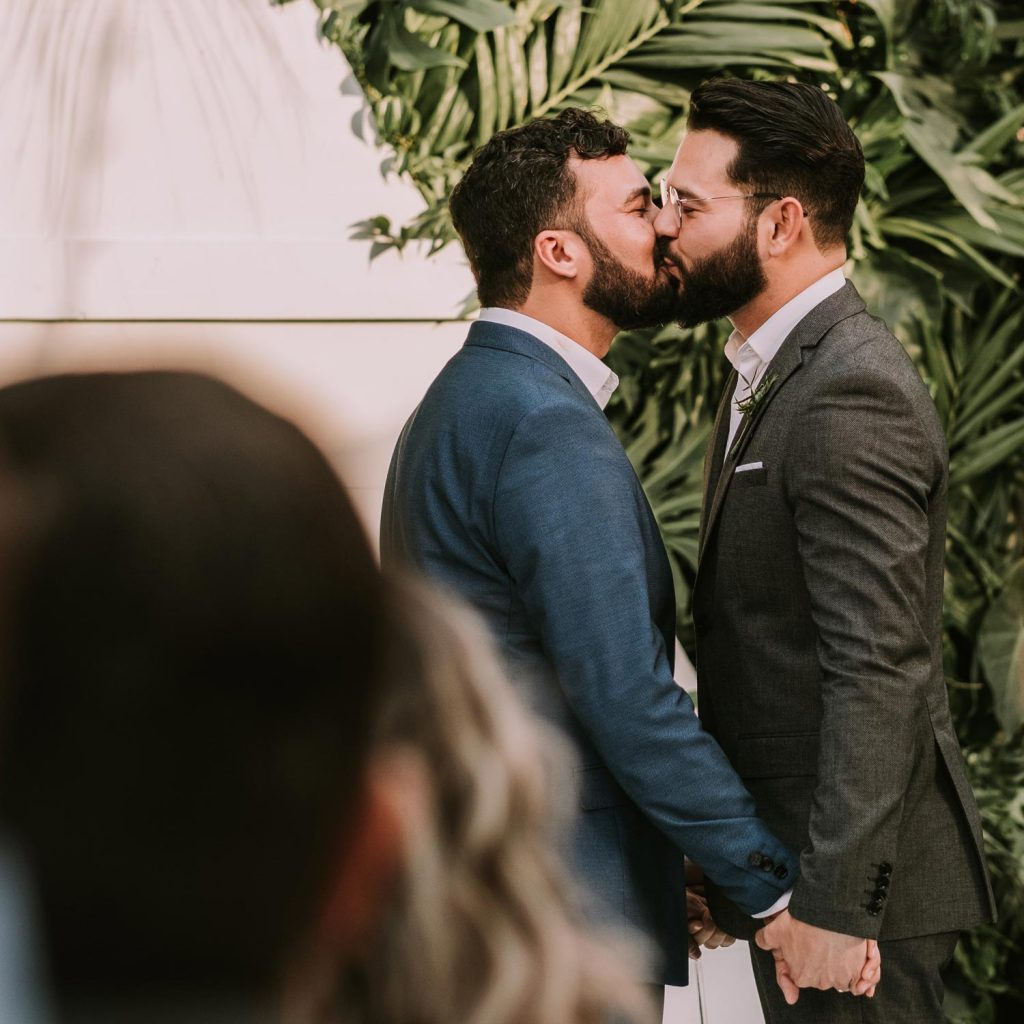 Same sex male couple kissing during their eco and sustainable ceremony - I provide inclusive wedding planning services