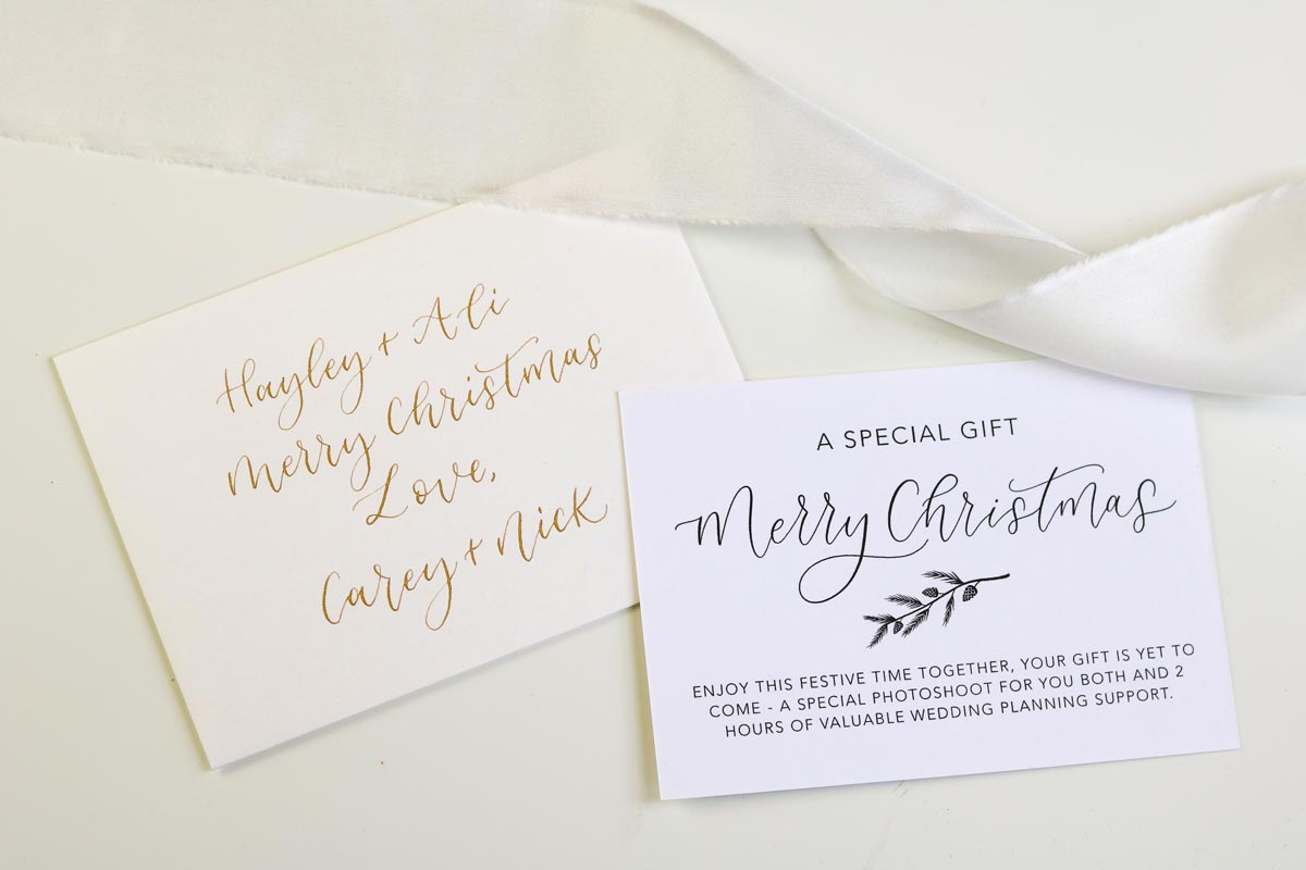 White voucher with black calligraphy and matching envelope addressed in gold calligraphy