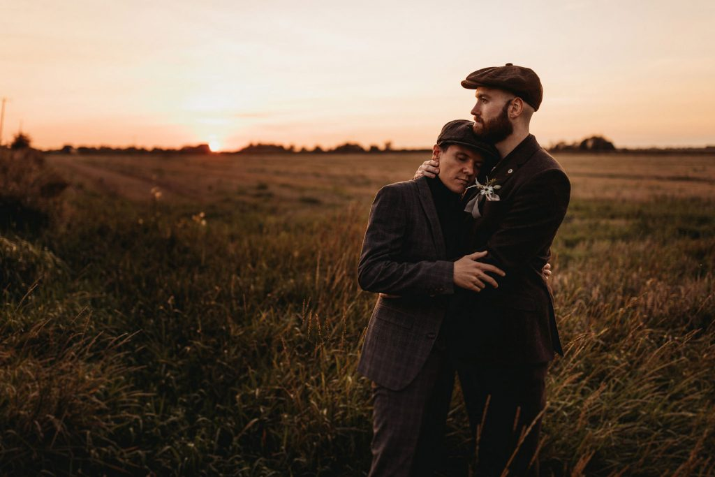 Husbands stood in an embrace in a field of long grass whilst the sun sets behind them