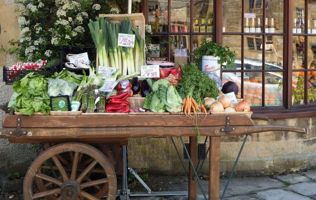 Wagon with fruit and vegetables outside a shop