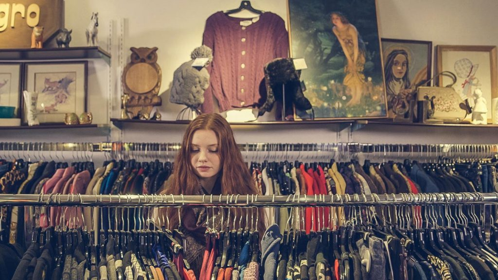 Lady stood amongst rails of clothing in a charity shop