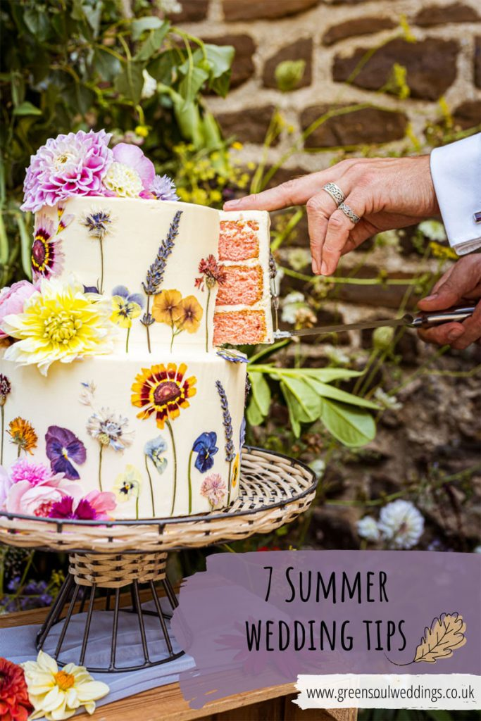 A 2 tier wedding cake with pressed flowers with one cut slice being removed by hand. The words 7 Summer Wedding Tips overlays the photo