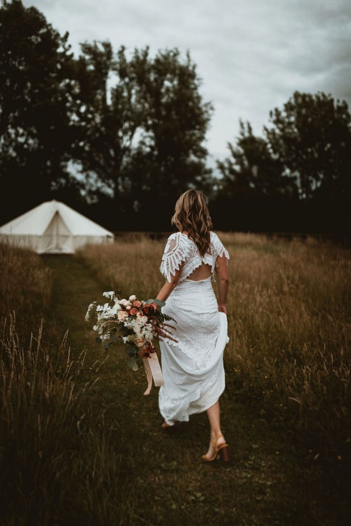 A lady in a wedding dress walks through a meadow towards a white bell tent