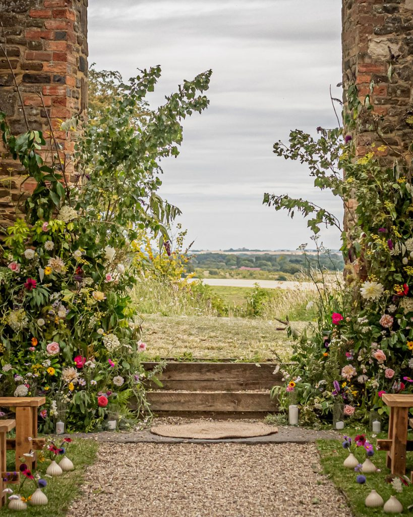 Looking through a church arch to an open view of fields and woodlands. The arch is decorated with colourful summer flowers on either side to frame the view