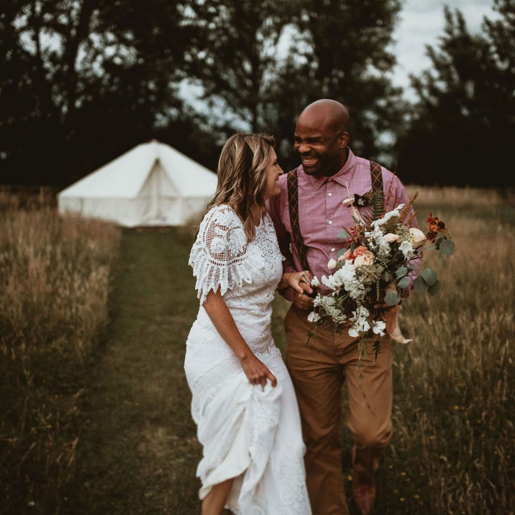 A newly married husband and wife share a laugh together whilst walking in a meadow at their outdoor wedding. Behind them is a glamping tent