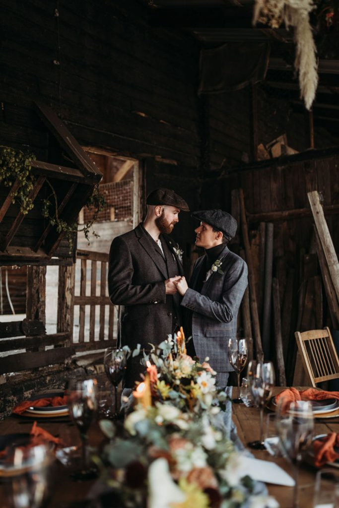 Male same sex couple holding hands and looking at each other as they stand amongst their rustic barn wedding reception