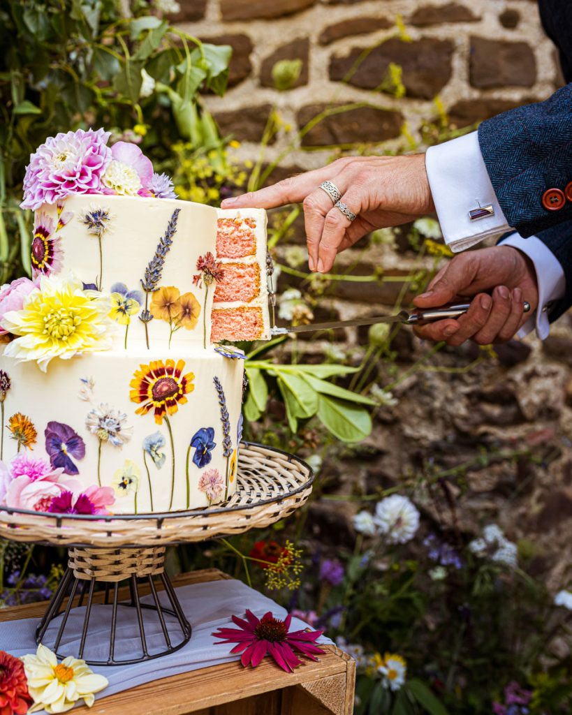 A slice of cake is being removed form the top tier of a wedding cake. The cake is decorated with pressed flowers and the sponge has a pale pink colour