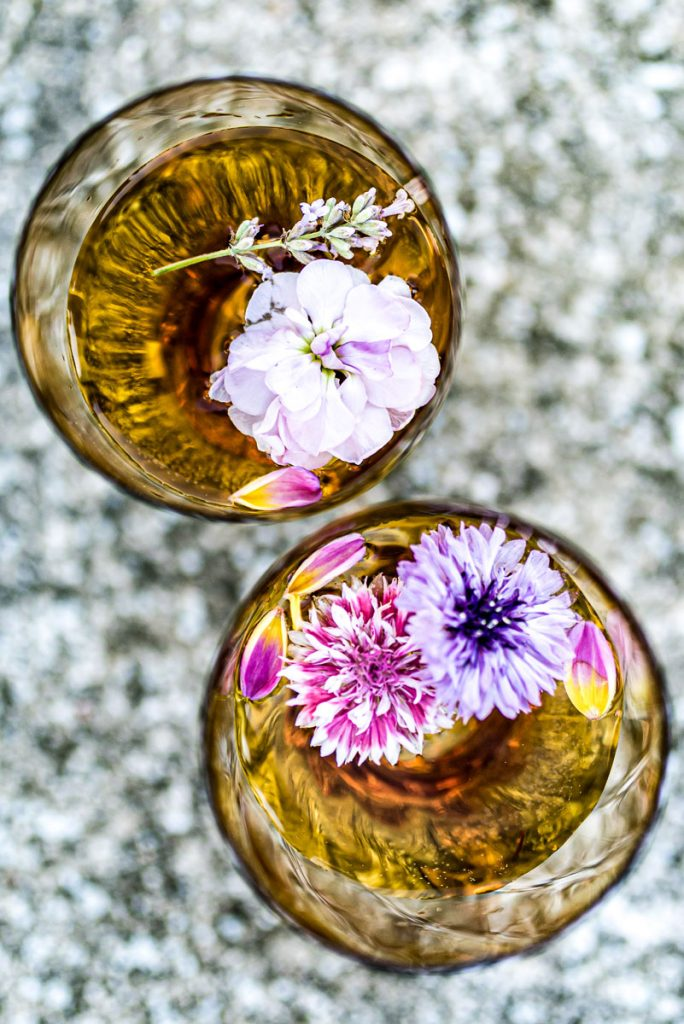Looking down on two golden coloured glasses containing a drink with delicate flowers floating in them