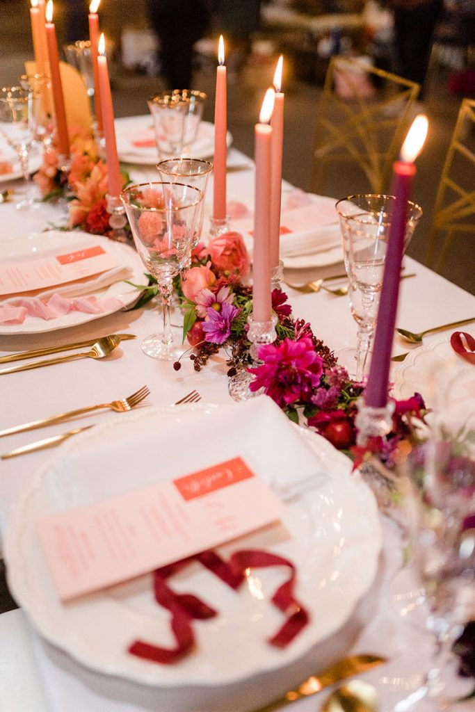 Long wedding table decorated with a floral runner down the centre. The flowers are styled in an ombre effect from purple through reds, pinks, oranges and into golden yellows. This is mirrored by the candles dotted along the table