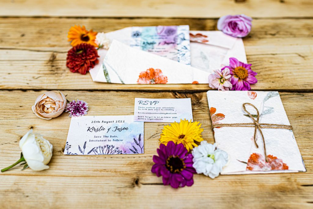 Save the date and other stationery elements for a summer wedding, decorated with floral details and printed on paper embedded with wildflower seeds