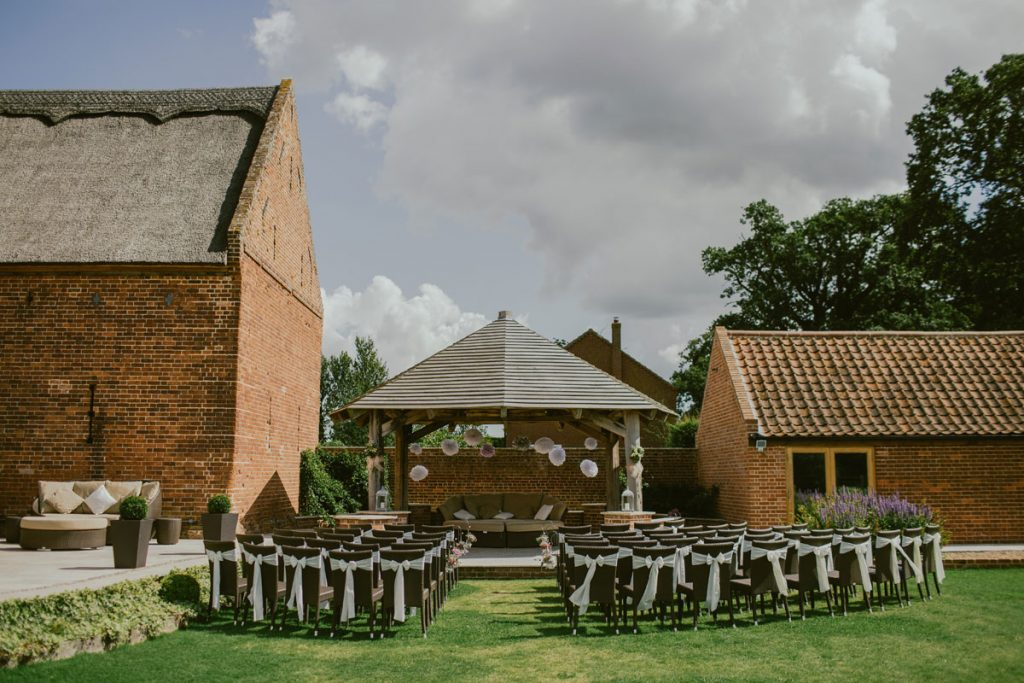 A venue with an outdoor open sided wooden structure for hosting a wedding. The chairs are set out on the grass in front of the structure