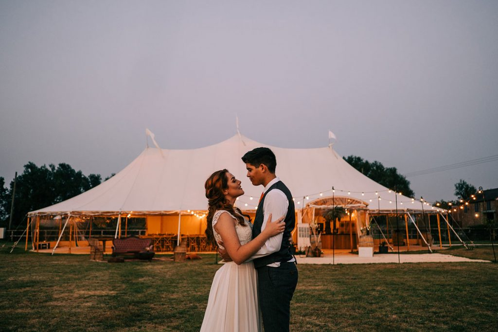 A couple stand in an embrace and look at each other in front of a large white canvas sperry tent