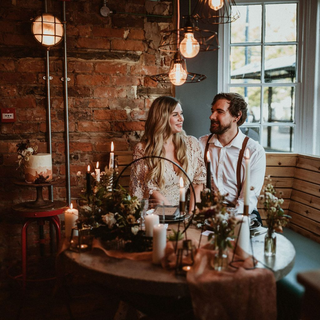 Couple sit at a decorated table in an urban cafe for their elopement wedding celebration. The cafe has an industrial feel with exposed brick walls, piping and metal lights.
