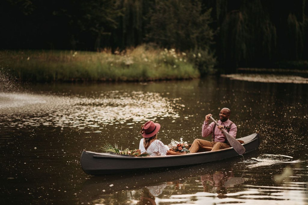 A couple enjoy a paddle in a rowing boat on a lake during their wedding celebrations