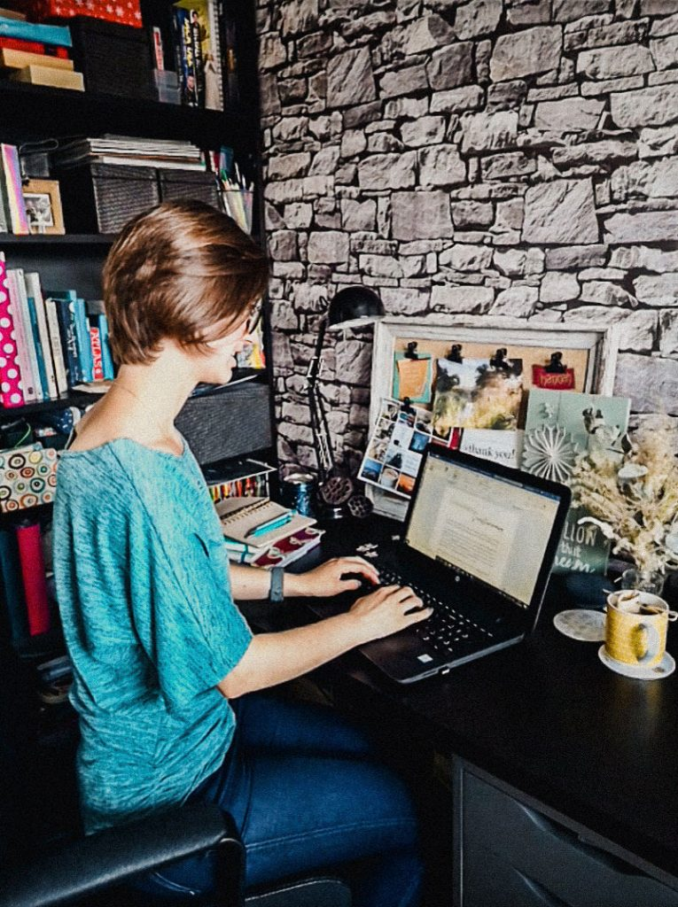 Wedding planner sat at her desk working on her laptop to create a detailed wedding day schedule