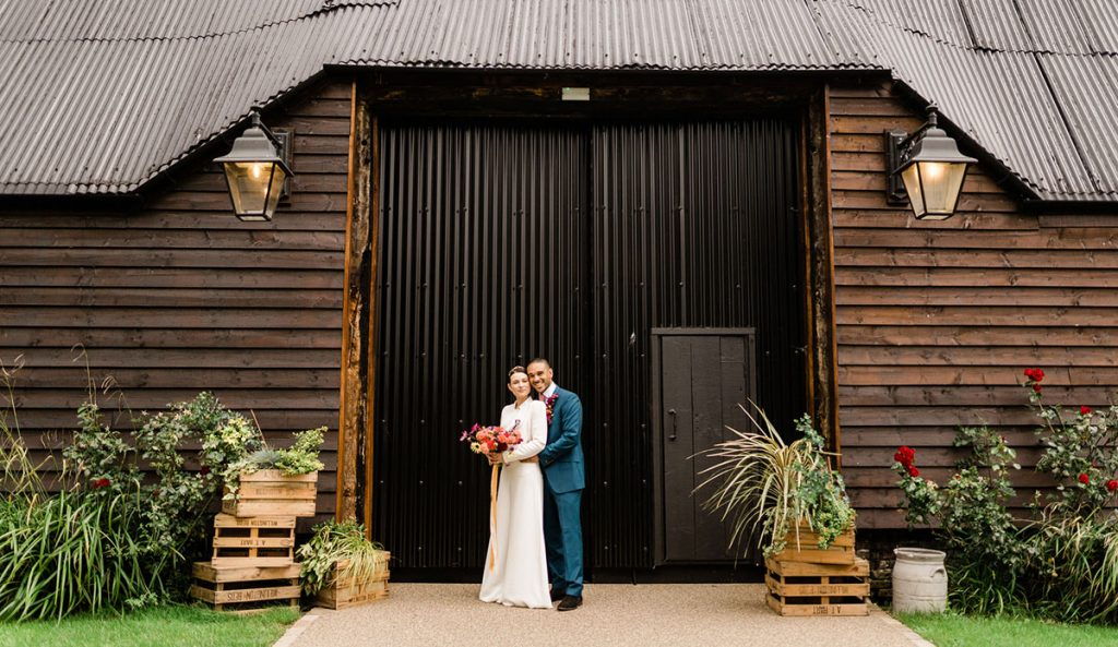 A couple pose for photos outside the large dark doors of their barn wedding venue in Cambridge