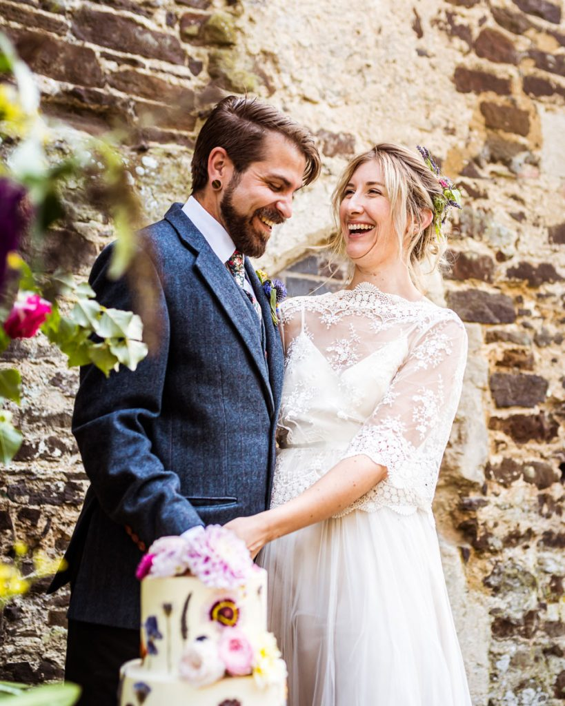 A relaxed couple laughing together whilst cutting their wedding cake