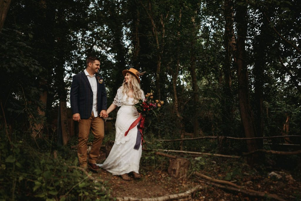 A just married couple walk hand in hand after their woodland ceremony