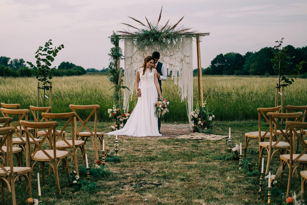 Newlywed couple stand at the top of the aisle by their macramé backdrop as they take a moment to reflect on their ceremony and wedding day so far