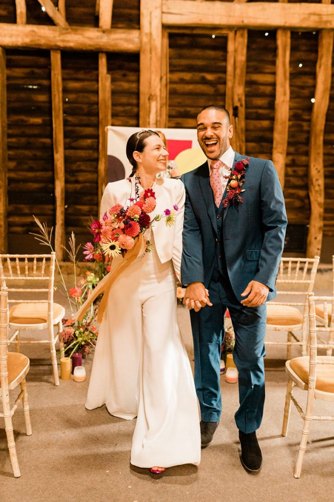 Newlywed couple walk back down the aisle full of excitement after their sustainable colourful barn wedding ceremony