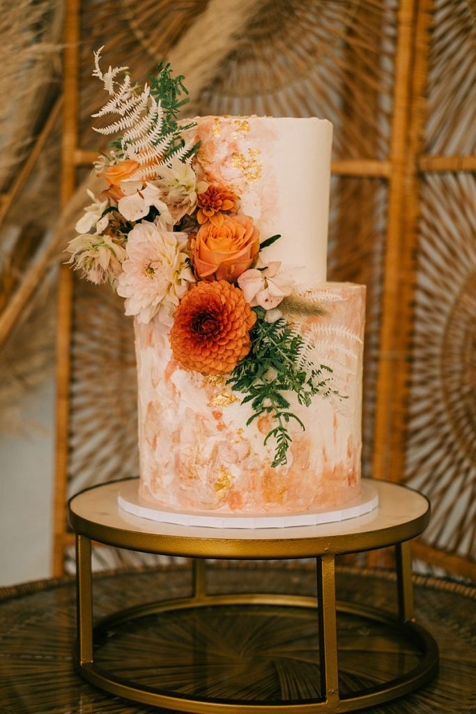 A white buttercream wedding cake with a textured peach and gold finish is decorated with orange, peach and white florals and upon a gold minimalist cake stand