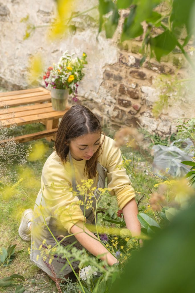 A sustainable florist creating a foam free floral structure of wild and locally grown flowers