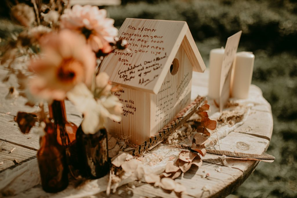 A wooden bird box is used as a guest book, with guests signing and leaving messages on this sustainable keepsake