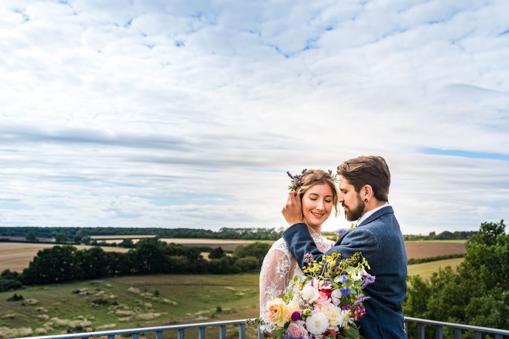 A bride and groom enjoy a peaceful moment at the top of the Clophill church tower with beautiful views