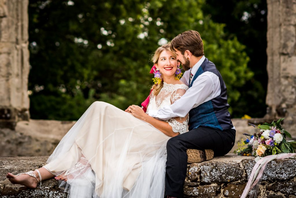 A couple relax at the church ruins of this unique sustainable wedding venue