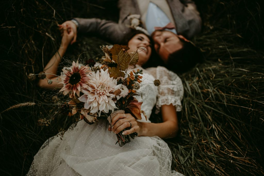 Newlywed couple lay in a meadow with their heads together, smiling at each other