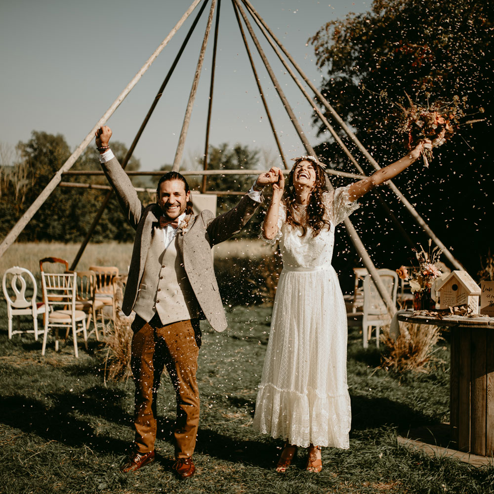 Newlyweds are showered in natural petal confetti after their outdoor laid-back ceremony