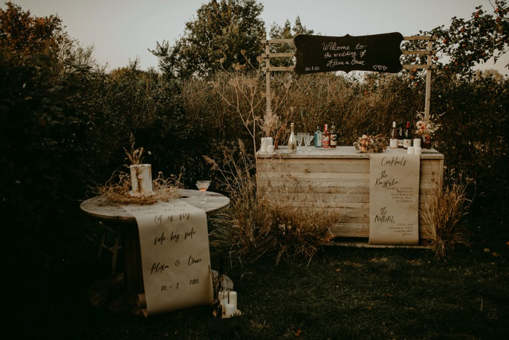 An outdoor wooden bar is decorated for an intimate sustainable wedding, with kraft paper menus and dried flowers