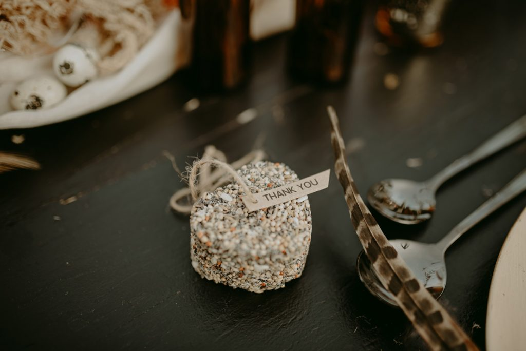 A heart shaped bird seed feeder is being given as a favour to wedding guests, laying by each table place setting and each with a 'Thank You' tag attached