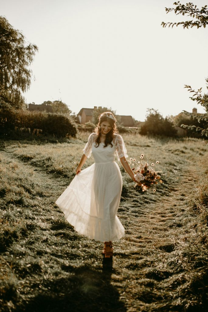 A bride walks through a meadow swirling her vintage lace wedding dress around with her bouquet in her hand