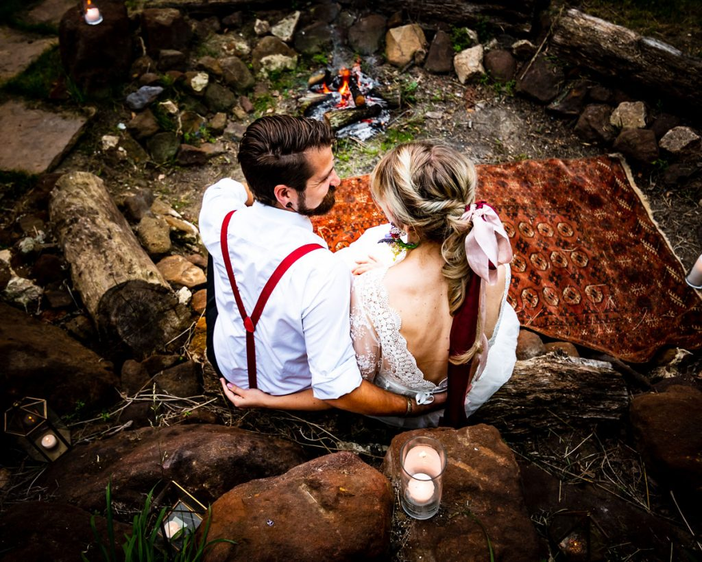 A bride and groom enjoy a moment by the firepit after their sustainable wedding celebrations