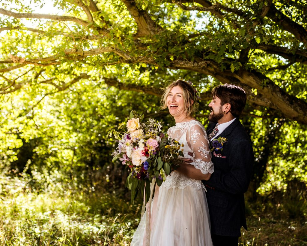 A married couple enjoy a laugh together in the trees after their sustainable wedding ceremony