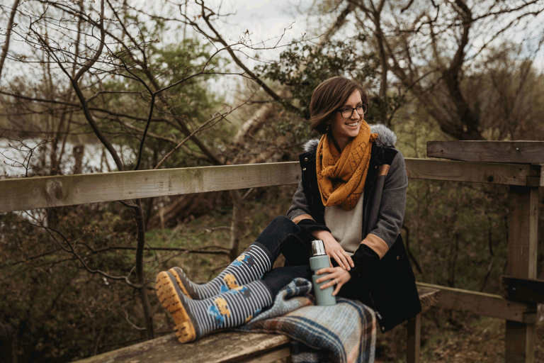 Hannah is a white young female and sits upon a wooden bench surrounded by trees and a lake. She wears a coat, floral blue and yellow wellies, jeans, and is holding a pale blue flask.